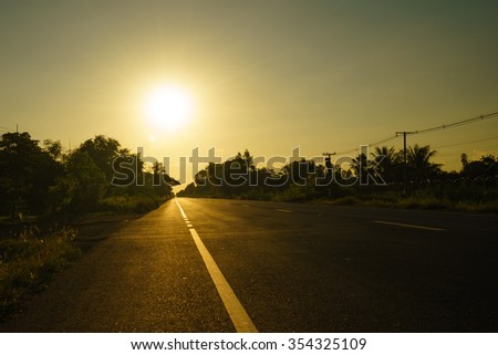 Straight Road at sunset in rural Thailand. - stock photo