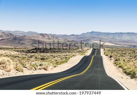 Straight road between hills in desert - stock photo