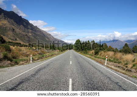 Straight road next to The Remarkables mountains in New Zealand