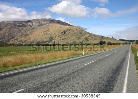 Straight road next to The Remarkables mountains in New Zealand - stock photo