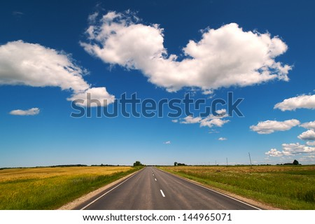 Straight road under blue sky in nice summer day.
