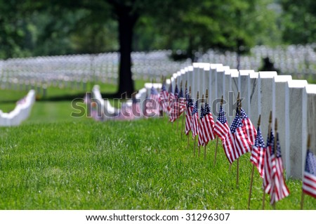Straight row of graves at the Arlington National Cemetery in Arlington, Virginia, near Washington DC, on Memorial Day, with flags at each grave, narrow DOF - stock photo