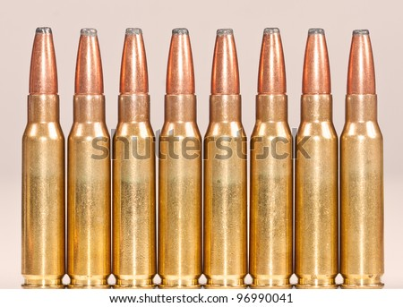 Straight row of rifle bullets on a pinkish background - stock photo
