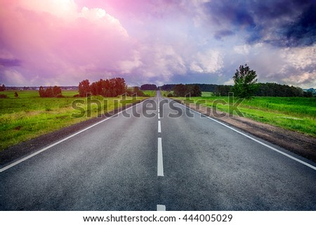 straight rural road at the sunset with a dramatic sky - stock photo