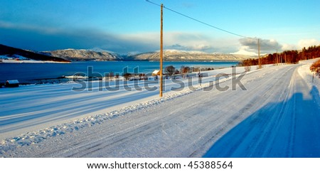 Straight snowy road on sunny day in Norway, winter - stock photo