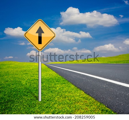 straight traffic sign pole beside asphalt road and blue sky with green grass - stock photo