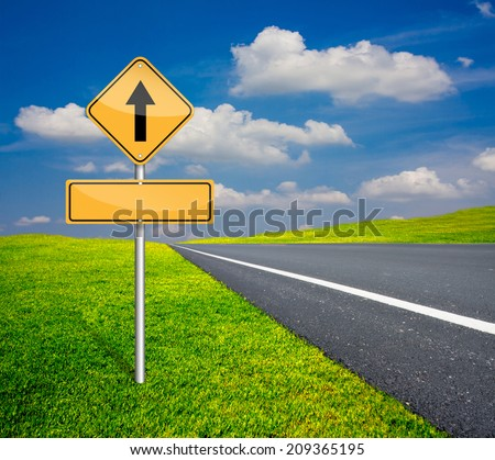 straight traffic sign with blank signs beside asphalt road and blue sky with green meadow - stock photo