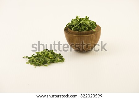 Straight view on shredded pandan leaf in a wooden bowl at right side with some outside the bowl. The leaf is use as herbal tea for its strong sweet fragrance and medicinal benefits.  White background. - stock photo