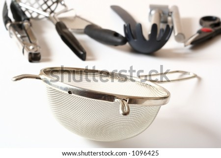 Strainer and other kitchen utensils in the background. - stock photo