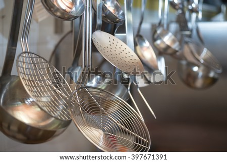 strainers ladles and kitchen accessories hanging - stock photo