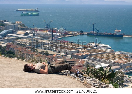 Strait of Gibraltar and middle aged woman tourist resting on the Rock of Gibraltar. - stock photo