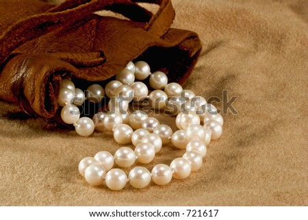 Strand of pearls spilling from a leather pouch.  On a seude background.