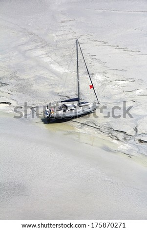 Stranded boat near the abbey Mont Saint Michel waits tide, to set sail. Normandy, France - stock photo