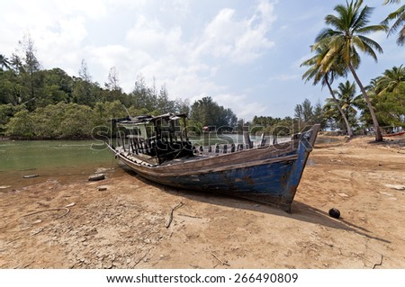 Stranded Fishing Boat at Terengganu, Malaysia during Sunny day. Image has grain or blurry or noise and soft focus when view at full resolution.  (Shallow DOF, slight motion blur) - stock photo