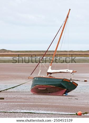Stranded sailing boat at low tide on the river Torridge in Devon UK - stock photo