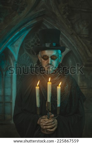 Strange and scary man standing with a candelabrum in which candles are burning. Men behind the old castle. - stock photo