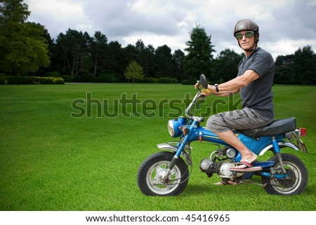 Strange biker sitting on a blue moped in countryside. - stock photo