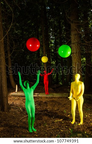 Strange, colorful people playing with balls in a dark wooded forest. - stock photo