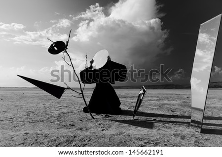 Strange figure in black cloak with the mirror face in desert. Artwork - stock photo