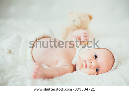 strange, funny portrait dreamy  little baby (child, kidd, infant) lying in a carpet. newborn. son. boy. - stock photo