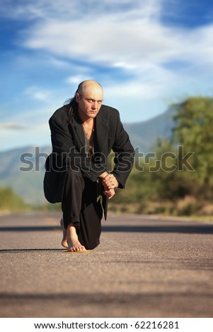 Strange indigenous man in the middle of a road - stock photo