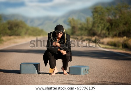 Strange indigenous man in the middle of a road with suitcases - stock photo