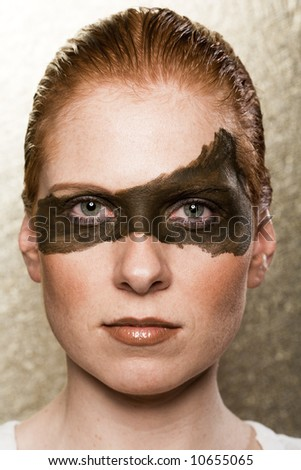 Strange Make-up on a woman's face. Big dark stripe over both eyes. Strict hairs. - stock photo