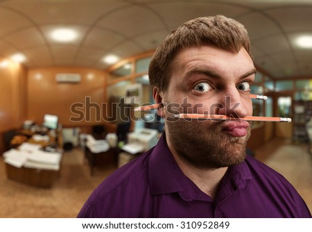 Strange man holds pencil with his nose and lips - stock photo