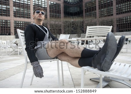 strange silly funny man wearing black coat shouting sitting on the street cafe - stock photo