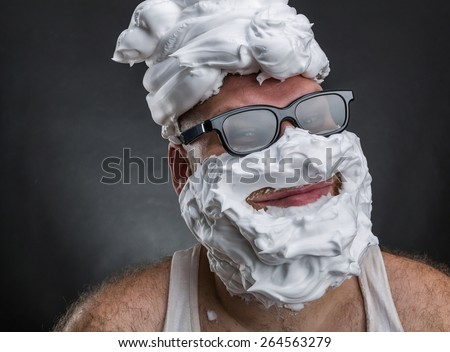 Strange smiling man in glasses with shaving foam on his face and on his head closeup - stock photo