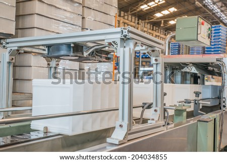 Strapping Machine for Industrial Packaging Line - stock photo