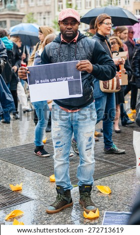 STRASBOURG, FRANCE - APR 26 2015: I am a migrant poster holed by a man at protest against immigration policy and border management which asks for commitment in the wake of migrants boat disasters - stock photo