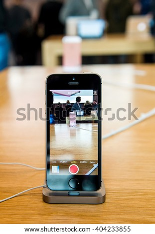 STRASBOURG, FRANCE - APR 9, 2016: New iPhone SE in docking station recording Apple Store with camera app. New Apple iPhone tends to become one of the most popular smart phones in the world. - stock photo