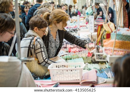 STRASBOURG, FRANCE - APR 24, 2016: People buying diverse accesories at traditional textile covered market with multiple different colors and textures