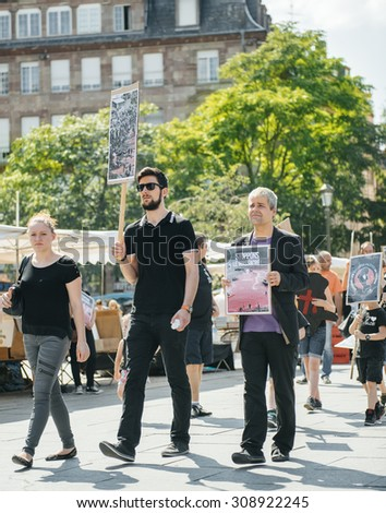 STRASBOURG, FRANCE - AUG 22, 2015: Marine conservation organization Sea Shepherd protesting against the slaughter of pilot whales and arrest of 7 crew members - solidarity group holding placards - stock photo