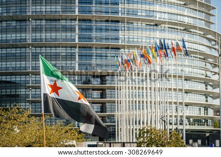 STRASBOURG, FRANCE - AUG 20, 2015: People protesting in front of European Parliament denouncing the Syrian airstrikes on Douma wheremore 80 were killed - All European Union flags and Syrian flag - stock photo
