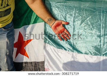 STRASBOURG, FRANCE - AUG 20, 2015: People protesting in front of European Parliament denouncing the Syrian airstrikes on Douma wheremore 80 were kille - syrian war Tattoo on hand and Syrian flag - stock photo