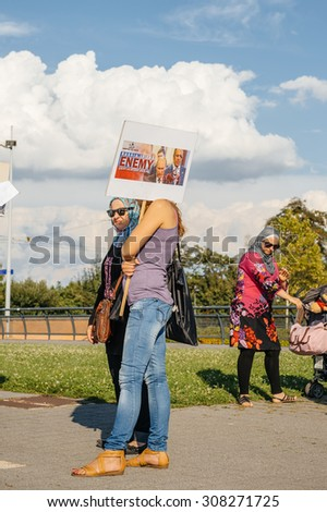 STRASBOURG, FRANCE - AUG 20, 2015: People protesting in front of European Parliament denouncing the Syrian airstrikes on Douma wheremore 80 were kille - Russia is the enemy placard - stock photo