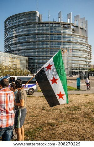 STRASBOURG, FRANCE - AUG 20, 2015: People protesting in front of Parliament denouncing Syrian airstrikes on Douma wheremore 80 were killed - flag of Syria with Parliament building in the background - stock photo