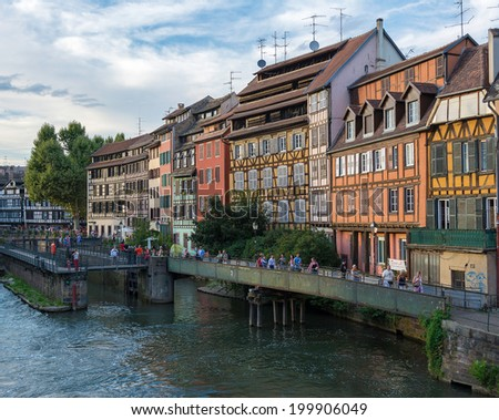 STRASBOURG, FRANCE - AUGUST 17, 2013: Tourists walking around Petite-France (Little France) in Strasbourg. Petite-France is an historic area in the center of Strasbourg.