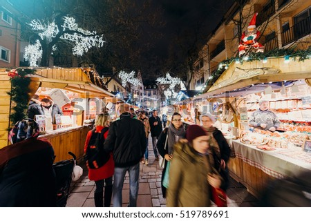 STRASBOURG, FRANCE - DEC 6, 2015: Adults, childrens, grandparents and happy people walking during Christmas Market admiring market stall, buying food, presents and toys