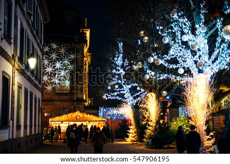 STRASBOURG, FRANCE - DEC 20, 2016: Beautiful Christmas Market atmosphere with tourists and locals admiring the MArket and MARket stalls and huge Christmas light being projected on the building