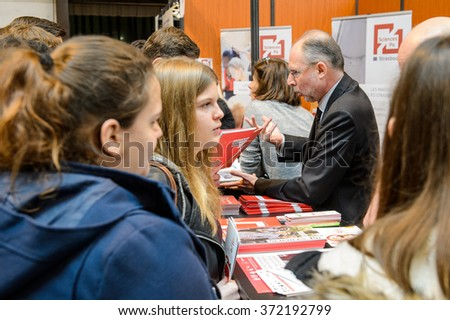 STRASBOURG, FRANCE - FEB 4, 2016: Children and teens of all ages attending annual Education Fair to choose career path and receive vocational counseling - professor explaining - stock photo