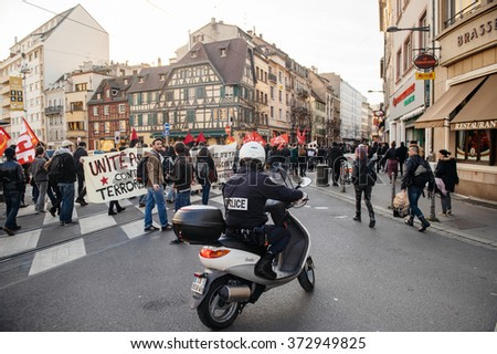 STRASBOURG, FRANCE - FEB 6, 2016: Police surveilling protesters marching during a demonstration against government's plan to extent the 'state of emergency' and for opened borders - stock photo