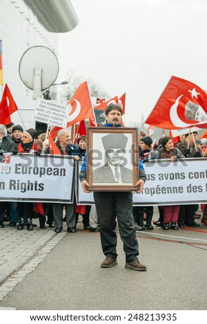 STRASBOURG, FRANCE - 28 JAN 2015 Man holding Ataturk portrait at demonstration near European Court before the Perincek vs. Switzerland case begin. Armenian government was represented by Amal Clooney - stock photo