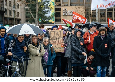 STRASBOURG, FRANCE - JAN 30 2016: Protesters gathered at Kleber Square protesting government's plan of the extension of the 'state of emergency' for another three months - people under rain at protest