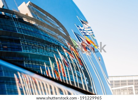 STRASBOURG, FRANCE - JANUARY 28, 2014: European flags and building of the European Parliament reflected in a car windshield parked near to the building.  - stock photo