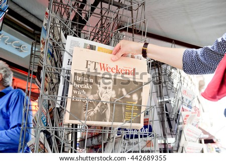STRASBOURG, FRANCE - JUN 25, 2016: Woman buying Financial Times newspaper with shocking James Cameron PM headline titles at press kiosk about the Brexit requesting to quit the European Union - stock photo