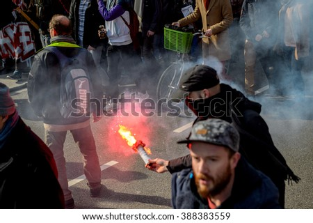 STRASBOURG, FRANCE - 9 MAR 2016: Man with red signal fire torch in city center as thousands of people demonstrate as part of nationwide day of protest against labor reforms by Socialist Government