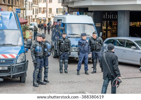 STRASBOURG, FRANCE - 9 MAR 2016: Police officers surveilling street as thousands of people demonstrate as part of nationwide day of protest against proposed labor reforms by Socialist Government - stock photo